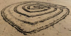 A maze scratched into the sand at a beach