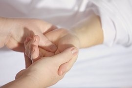 photo of hands massaging someone elses hand