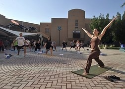 woman leading a yoga class on a mosaic are in town square type area